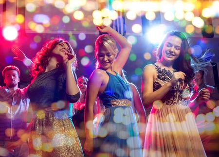 party, dovolená, oslava, noční život a lidé koncepce - usmívající se přátelé tančí v klubu