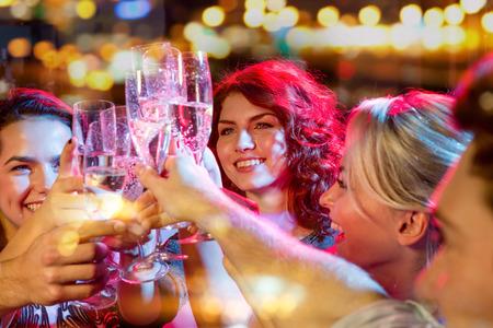 gente celebrando: fiesta, d�as de fiesta, celebraci�n, vida nocturna y la gente conceptuales - amigos sonrientes con copas de champ�n en el club Foto de archivo