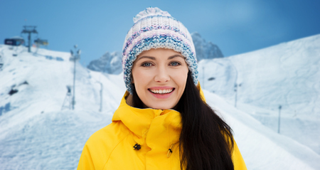 downhill skiing: winter, leisure, clothing and people concept - happy young woman in winter clothes over downhill skiing and mountains background