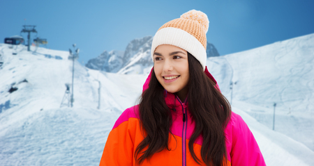 downhill skiing: winter, leisure, clothing and people concept - happy young woman or teenage girl in winter clothes over downhill skiing and mountains background