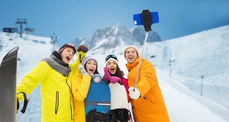 leisure: winter sport, leisure, friendship, technology and people concept - happy friends with snowboards and taking picture by smartphone on selfie stick over downhill skiing and mountains background Stock Photo