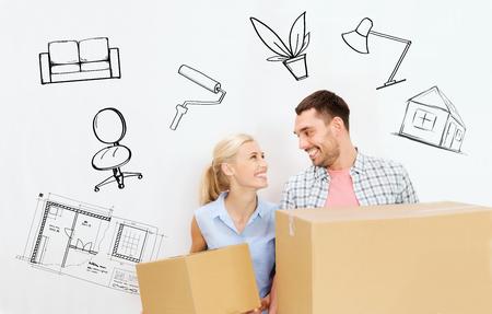家、人、修理および不動産コンセプト - 幸せなカップルの段ボール箱を押しながらインテリアの上に新しい場所に移動背景をいたずら書き 写真素材