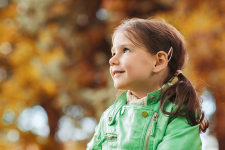 girl looking up: autumn, season, childhood, happiness and people concept - happy beautiful little girl portrait outdoors