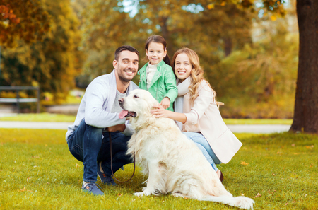 little  girls: family, pet, domestic animal, season and people concept - happy family with labrador retriever dog on walk in autumn park
