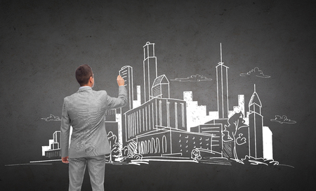 architectures: business, people, architecture and real estate concept - businessman drawing city sketch from back over dark gray concrete wall background