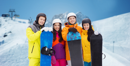 downhill skiing: winter, leisure, extreme sport, friendship and people concept - happy friends in helmets with snowboards over downhill skiing and mountains background