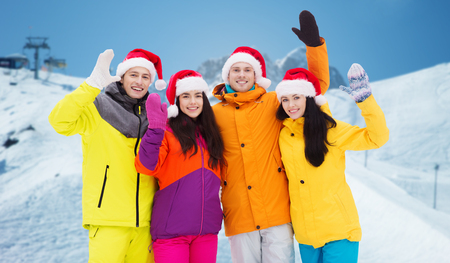downhill skiing: winter holidays, christmas, friendship and people concept - happy friends in santa hats and ski suits over downhill skiing and mountains background Stock Photo