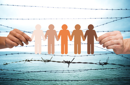 imprisonment: crime, imprisonment, refugee and humanity concept - multiracial couple hands holding chain of paper people pictogram over sea and barb wire background