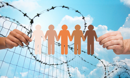 refugee: crime, imprisonment, refugee and humanity concept - multiracial couple hands holding chain of paper people pictogram over blue sky and barb wire background