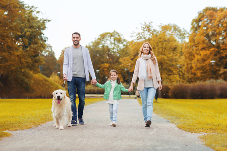 animal family: family, pet, domestic animal, season and people concept - happy family with labrador retriever dog walking in autumn park