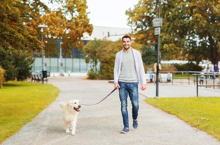 parken: Familie, Haustier, Haustier, Jahreszeit und Personen-Konzept - glücklicher Mann mit Labrador Retriever Hund zu Fuß im Herbst Stadtpark