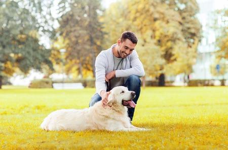 familie, huisdier, huisdier, het seizoen en de mensen concept - gelukkig man met een labrador retriever hond wandelen herfst in stadspark