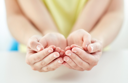persona feliz: la gente, la caridad, la familia y la publicidad concepto - cerca de la mujer y la niña somethining sosteniendo en manos ahuecadas