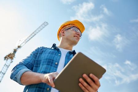 operarios trabajando: negocio, la construcción, la industria, la tecnología y el concepto de la gente - constructor sonriente en el casco con el equipo de PC de la tablilla sobre grupo de constructores en el emplazamiento de la obra