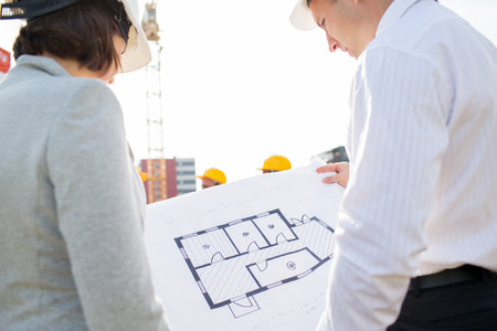 construction plans: construction, architecture, business, teamwork and people concept - close up of architects with blueprint at building site