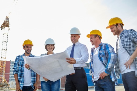 sites: business, building, teamwork and people concept - group of builders and architects in hardhats with blueprint on construction site