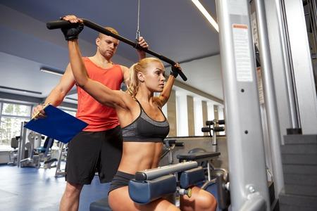 fortaleza: deporte, gimnasio, trabajo en equipo y la gente concepto - mujer flexionando los músculos pequeños en la máquina de gimnasio y entrenador personal con el portapapeles