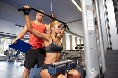 sport, fitness, teamwork and people concept - young woman flexing muscles on gym machine and personal trainer with clipboard