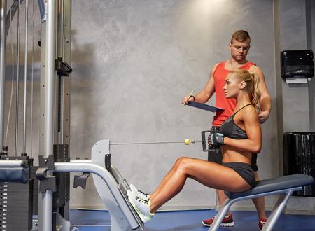 trabajo en equipo: deporte, gimnasio, trabajo en equipo y la gente concepto - mujer joven y entrenador personal que dobla los m�sculos en el gimnasio de la m�quina de cable