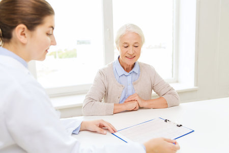 age care: medicine, age, health care and people concept - doctor with clipboard and senior woman meeting at hospital