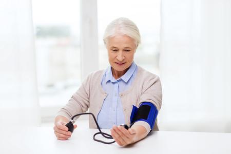 hipertension: la medicina, la edad, la salud y las personas concepto - mujer mayor con el tonómetro de comprobar el nivel de presión arterial en el hogar Foto de archivo