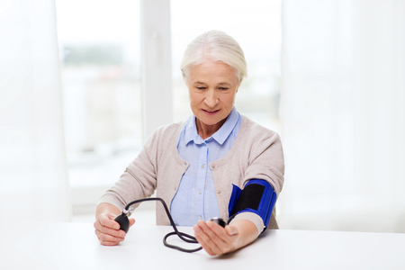 tonometer: medicine, age, health care and people concept - senior woman with tonometer checking blood pressure level at home