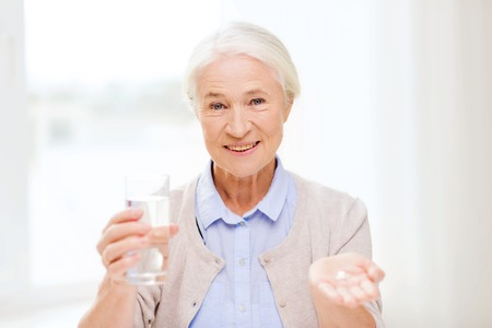 old age care: age, medicine, health care and people concept - happy senior woman with pills and glass of water at home