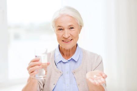 leeftijd, geneeskunde, gezondheidszorg en mensen concept - gelukkig senior vrouw met pillen en glas water thuis