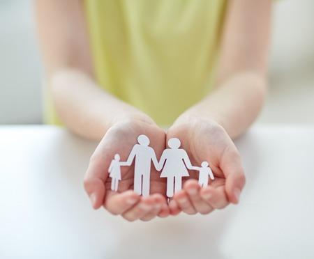 planificacion familiar: la gente, la caridad y el cuidado concepto - cerca de los niños tomados de la mano del recorte de papel de la familia en el hogar