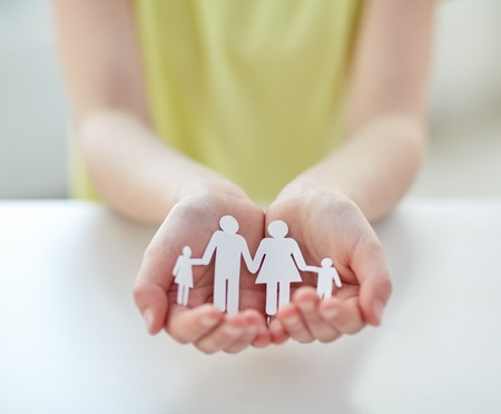 holding mother's hand: people, charity and care concept - close up of child hands holding paper family cutout at home