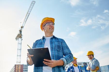 、ビジネスの構築、事務処理や人々 のコンセプト - クリップボードと建設現場で建設業者のグループに鉛筆でヘルメットで幸せなビルダー