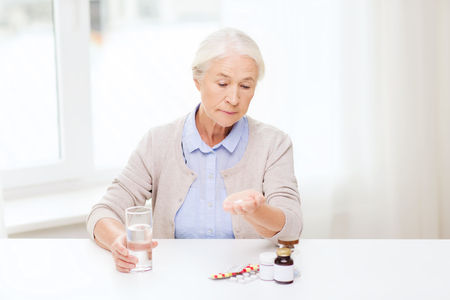 persona de la tercera edad: age, medicine, health care and people concept - senior woman with pills and glass of water at home Foto de archivo