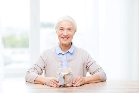 frasco: ahorros, dinero, seguros de rentas, la jubilación y el concepto de la gente - sonriente mujer mayor con el dinero en frasco de vidrio en el hogar