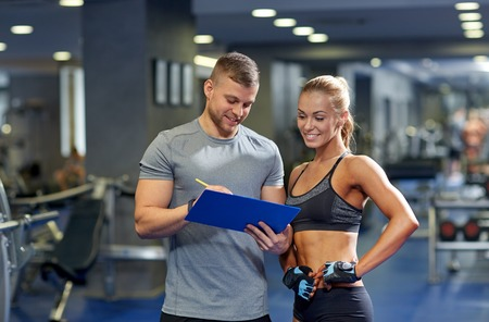 gym: fitness, sport, exercising and diet concept - smiling young woman and personal trainer with clipboard writing exercise plan in gym