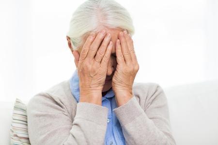 persona de la tercera edad: cuidado de la salud, el dolor, el estrés, la edad y las personas concepto - mujer mayor que sufre de dolor de cabeza o dolor
