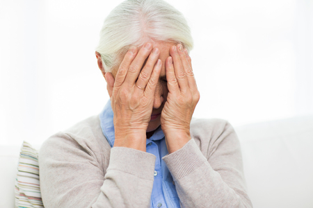 megrim: health care, pain, stress, age and people concept - senior woman suffering from headache or grief Stock Photo