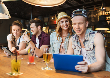 social networking: people, leisure, friendship and communication concept - group of happy smiling friends with tablet pc computer and drinks at bar or pub