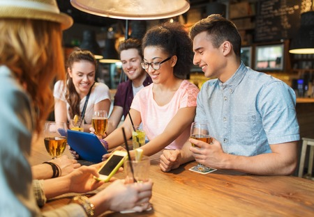 pub: people, leisure, friendship and communication concept - group of happy smiling friends with tablet pc computer and drinks at bar or pub