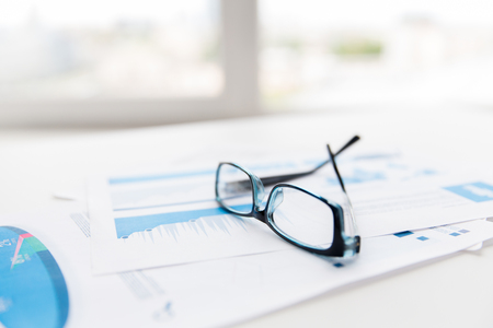 eyeglasses: business, objects and statistics concept - close up of eyeglasses and files on office table