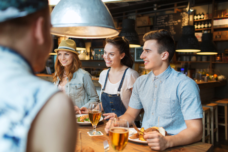 cocktail bar: people, leisure, friendship and communication concept - group of happy smiling friends eating, drinking and talking at bar or pub