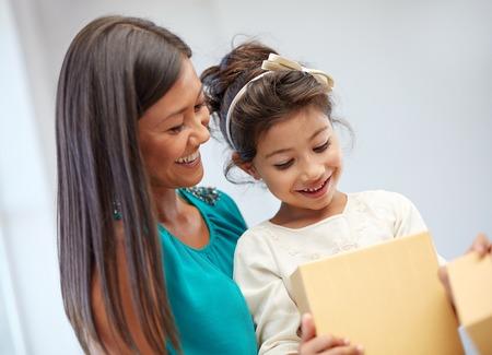 vakantie, verjaardag familie, jeugd en mensen concept - gelukkige moeder en meisje met gift box in huis