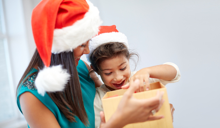 asian baby: christmas, holidays, family, childhood and people concept - happy mother and little girl in santa hats opening gift box at home