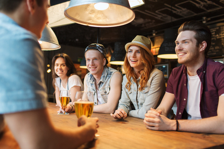 people, leisure, friendship and communication concept - group of happy smiling friends drinking beer and talking at bar or pub Stock Photo
