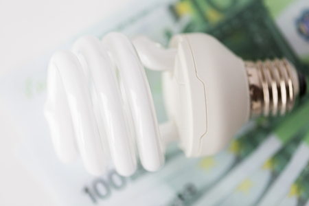 saving electricity: business, finance, energy saving and utilities concept - close up of euro paper money and light bulb on table