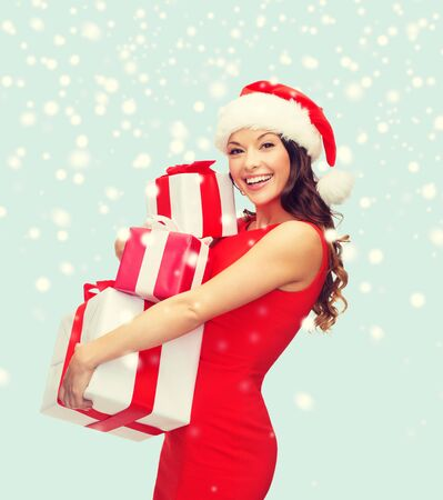 fancy box: christmas, x-mas, winter, happiness concept - smiling woman in santa helper hat with many gift boxes