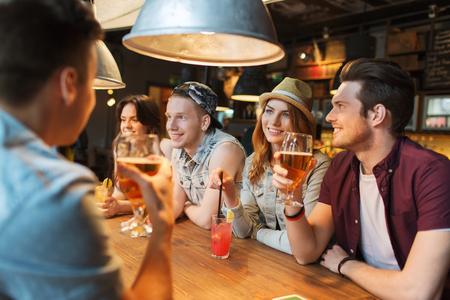 friendship: les gens, les loisirs, l'amitié et de la communication notion - groupe d'amis heureux sourire buvant de la bière et des cocktails parler au bar ou pub