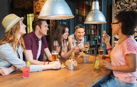 alcohols: people, leisure, friendship and communication concept - group of happy smiling friends drinking beer and cocktails eating and talking at bar or pub