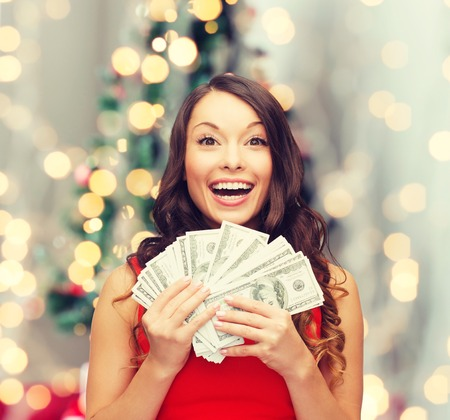 us money: christmas, sale, banking, winning and holidays concept - smiling woman in red dress with us dollar money over living room and christmas tree background