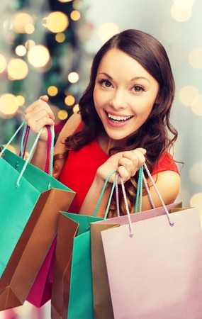 christmas shopping bag: sale, gifts, holidays and people concept - smiling woman with colorful shopping bags over living room and christmas tree background