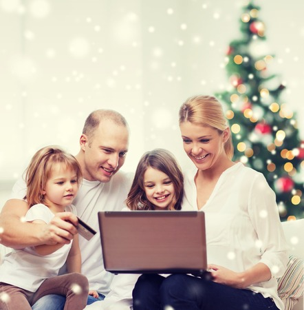shopping card: family, holidays, shopping, technology and people - happy family with laptop computer and credit card over living room and christmas tree and snow Stock Photo